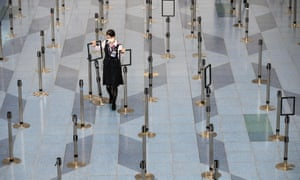 An airline employee in the deserted departure hall of Tokyo's Haneda airport.