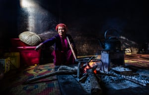 By Amy Sinead Moran. Palaung tribal village, Pein hnae bin. A woman of the Palaung tribe at home in her kitchen at dusk, the last light of the day coming in from the side window as she keeps the fire going to prepare dinner.