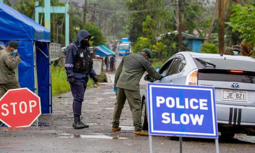 Police in Suva, Fiji, enforce mask protocols in a residential area