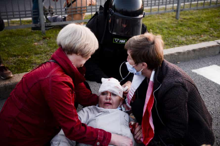 A police officer and two women help a woman injured in protests on Wednesday night in Minsk.