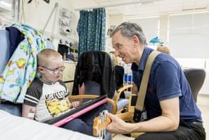 Ben Eccleston-Barnes, from Devon, is visited by volunteer music therapist Brian in Rose ward