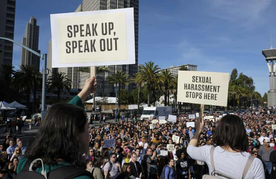 Google employees hold up signs during a walkout rally in San Francisco.