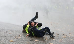 A couple of Gilet jaunes are felled by a water cannon.