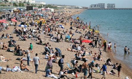 People sunbathe on Brighton beach.