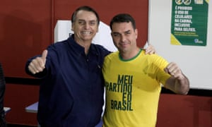 Jair Bolsonaro, Brazil's far-right presidential candidate, poses with his son Flavio, after casting his vote on 7 October in Rio de Janeiro.