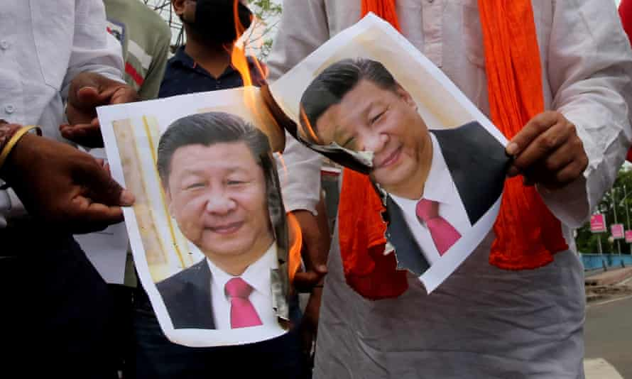 Photos of Chinese president Xi Jinping are burned during a protest in Bhopal, India, on Wednesday after Monday's fatal border clash.