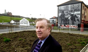 Ivan Cooper in the Bogside, Derry. In the background is the mural of Father Edward Daly holding a white handkerchief after British troops opened fire on demonstrators.