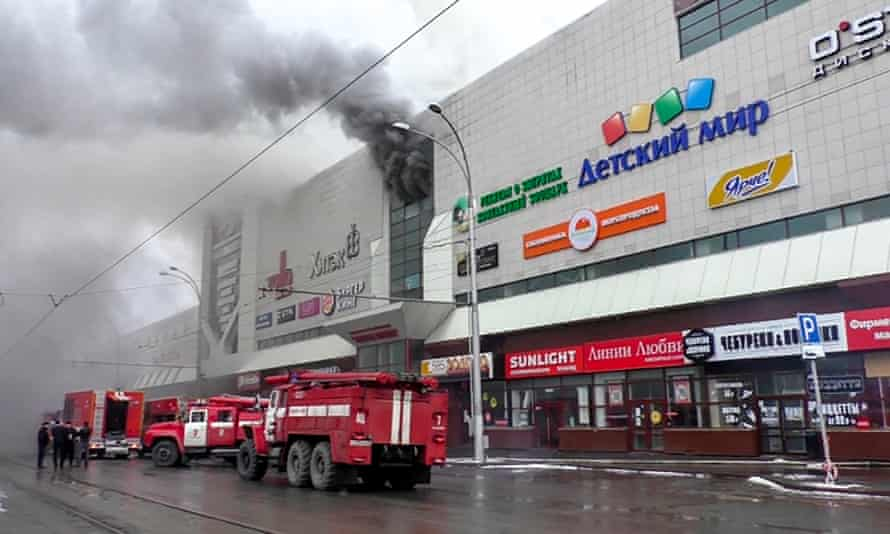 Emergency vehicles gather outside the burning shopping centre in Kemerovo.