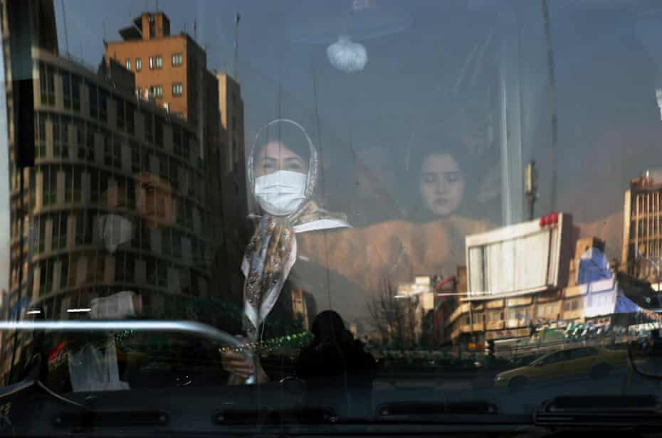An Iranian woman wearing a protective mask to prevent contracting coronavirus stands in a bus in Tehran.