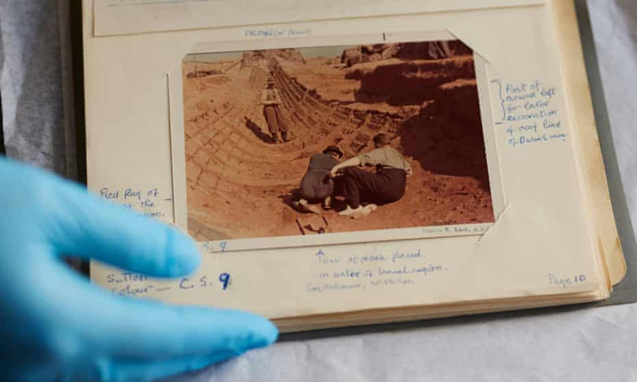 A colour photograph of two people at the dig being handled by a gloved archivist