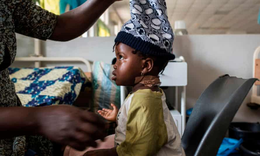 A young girl who was wounded in the neck with a machete during ethnic clashes sits in the Jos University Teaching Hospital.
