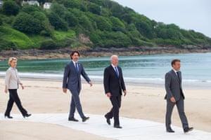 Canada's prime minister, Justin Trudeau, on the boardwalk behind Joe Biden and Emmanuel Macron