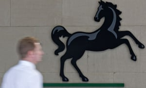 a man passes a Lloyds bank sign