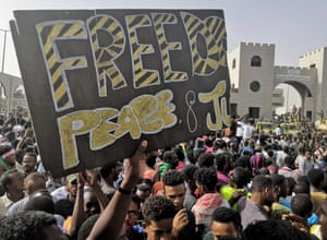 Sudanese anti-regime demonstrators hold up a banner calling for 'Freedom, Peace and Justice'