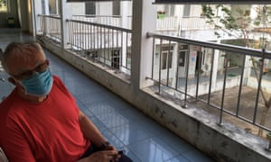 Graham Craddock wears a blue mask and sits on a balcony in Vietnam