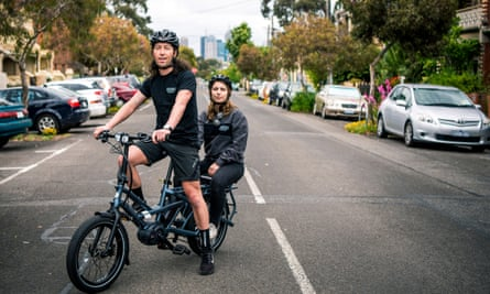 Jimmy Couling rides an e-bike with Stef De Stefano on the back in the streets of North Fitzroy in Melbourne