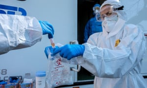 Health workers collect swabs to conduct tests on drivers for coronavirus disease in Rome, Italy.