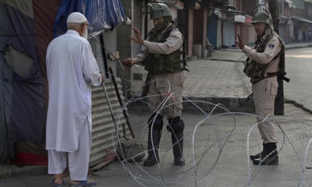 A Kashmiri man is stopped before being allowed to pass near a temporary checkpoint in Srinagar