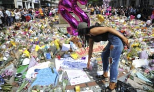 A woman looks at floral tributes in St Ann's Square, central Manchester