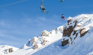 Someone on cable car and a snowboarder mid-air in Ohau snow fields