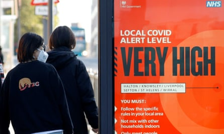 A person wearing a mask walks past a Covid warning sign in Liverpool