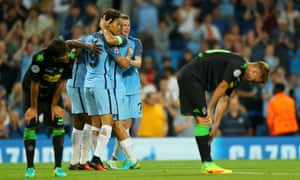 Manchester City players celebrate whilst the Borussia Moenchengladbach players look dejected.