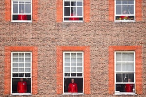 Chelsea pensioners watch a Remembrance Sunday service from their windows at the Royal Hospital Chelsea during the lockdown due to the coronavirus outbreak.