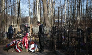 Relatives of Alexei Alekseyev, one of the plane crash victims, stands at his grave after the funeral at Bogoslovskoye cemetery