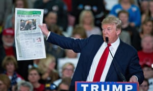 Donald Trump holds up a copy of the Wall Street Journal during a campaign rally on 24 November 2015 in Myrtle Beach, South Carolina.