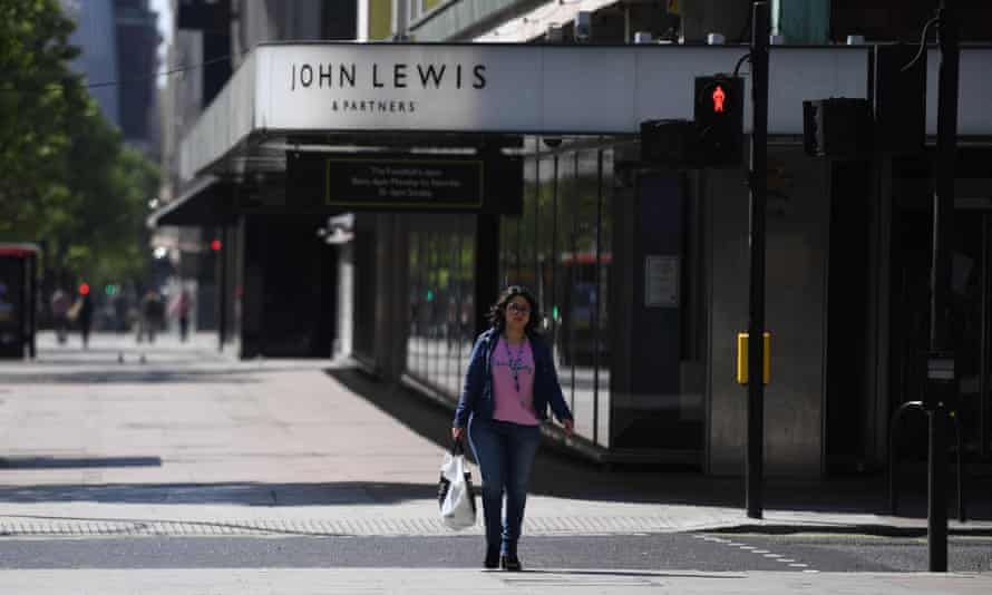A woman passes a closed John Lewis store on an empty Oxford Street in London