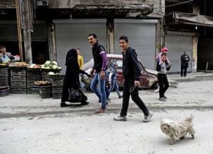 A man walks his dog in the al-Shaar neighbourhood