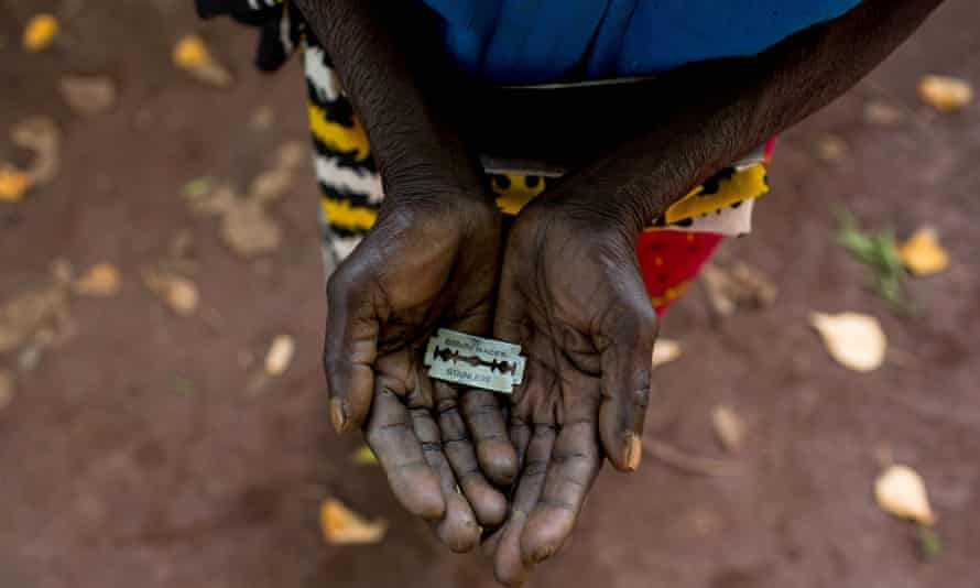 A woman in Kenya shows the razorblade she uses to cut girls' genitals