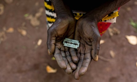 A cutter in Africa holds a razor blade she uses to carry out female genital mutilation.