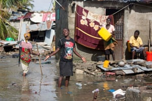 People walk around their destroyed houses in the water, in Beira, Mozambique, in March 2019 after Cyclone Idai destroyed most parts of the city
