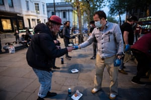 Volunteers with the charity Under One Sky give hot food and drink to homeless people in St Martins in the Fields, London.