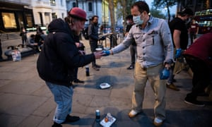 A volunteer for the Under One Sky charity hands out hot drinks and food to a homeless man in London.