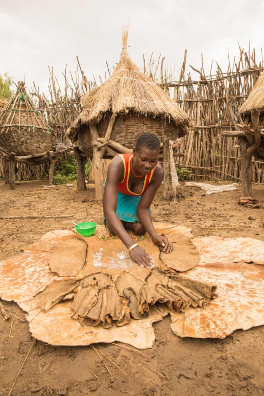 Lepera Joyce, 23, uses cow ghee to clean a goatskin skirt in Karamoja region, Uganda