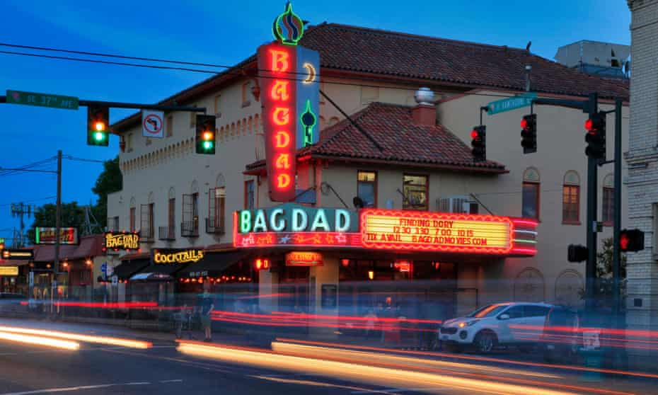 Neon sign of Bagdad Theatre and traffic blurs at night