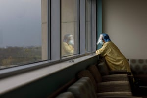 A healthcare worker pauses at a window