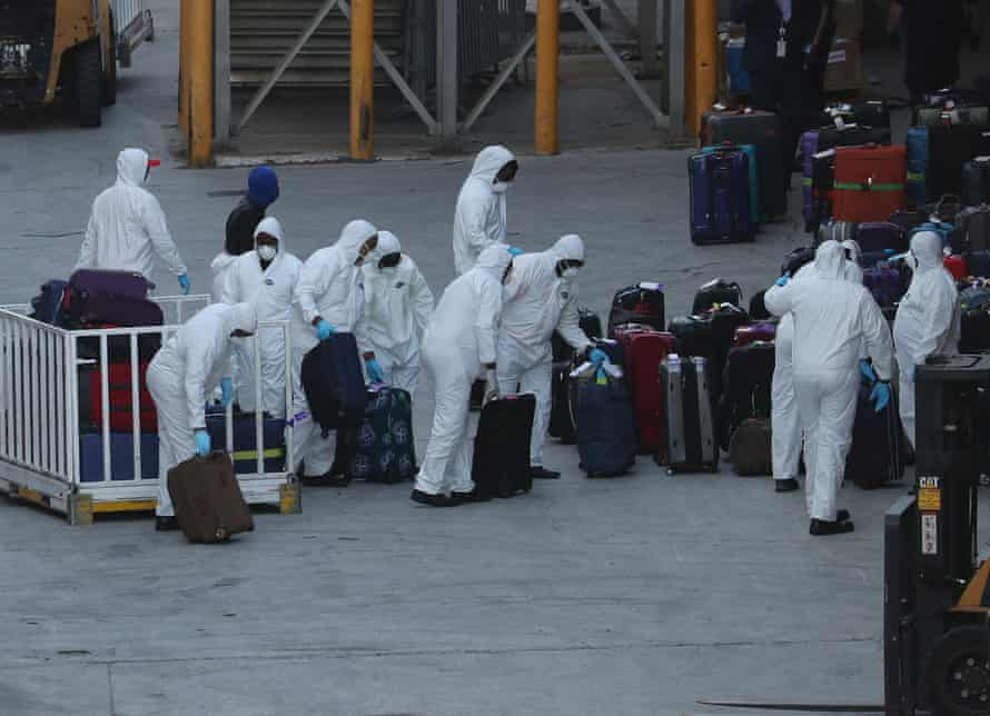 Workers dressed in hazmat suits take the luggage off the Zaandam cruise ship.