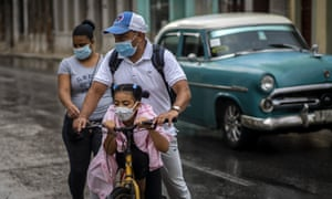 A girl wearing a mask against the spread of the new coronavirus is carried on the bicycle by her father in Havana, Cuba, Tuesday, Oct. 6, 2020.