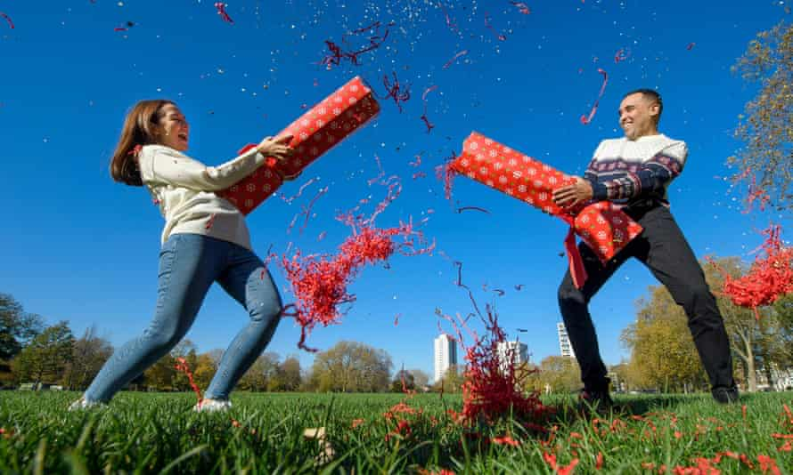 Two people pulling a giant Christmas cracker outdoors