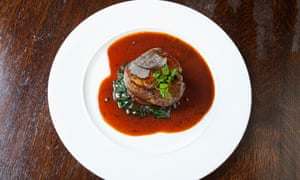 A thick steak in a red sauce on a round white plate
