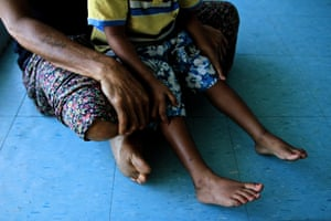 Paula and her son sit in a family and sexual violence refuge in Lae