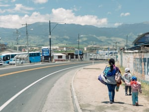 A Venezuelan mother walks with her two young children on the main road from the Ecuadorian border town of Tulcan towards Quito.
