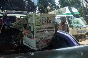Matatu driver reading newspaper with coronavirus news