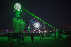 Music fans run from a laser beam designed to eradicate festivalgoers not dressed in denim hot pants