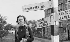 Barbara Pym, standing beside a direction signpost in the village of Finstock, Oxfordshire in 1979.