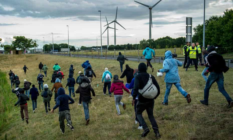 Migrants run pass police in Coquelles near Calais