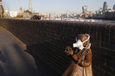 Greenpeace activists fit the statue of Doctor Salter's Daughter with an emergency face mask to demand action on air pollution.